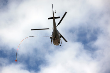 Rescue helicopter moving in blue sky with clouds
