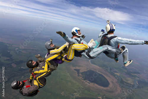 Five skydivers free-fall in the figure.