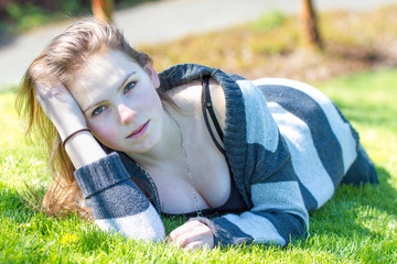 Attractive young caucasian female lies on grass