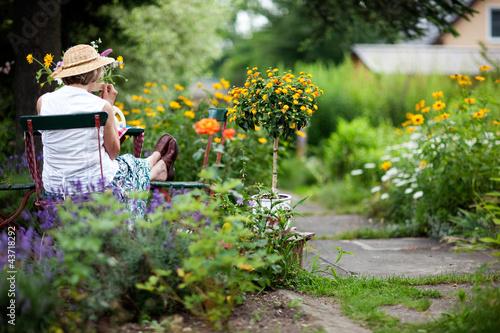 Seniorin im sommerlichen Garten Poster