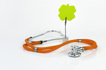 Orangefarbenes Stethoskop und grüner Notizzettel