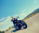 Biker riding a customized motorcycle on an open road