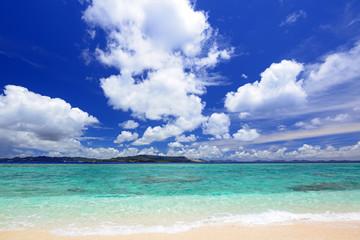 南国沖縄の美しいビーチに打ち寄せる透明な波と夏空