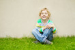 Smiling little boy sitting on grass against concrete wall