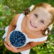 Lovely girl with fresh blueberries in the garden