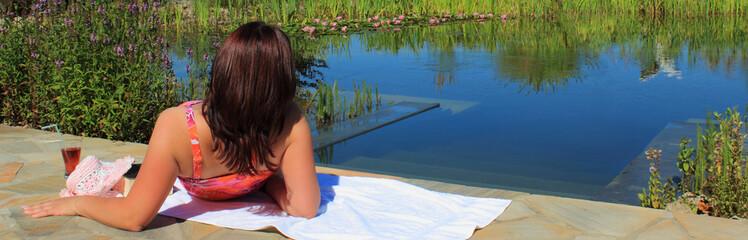 Junge Frau blickt über Schwimmteich