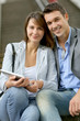 Cheerful couple sitting in stairs with electronic tablet