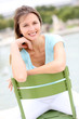 Beautiful woman sitting on chair in public park