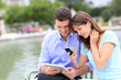 Couple using tablet and cellphone in public park