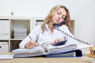 Frau am Telefon macht Notizen