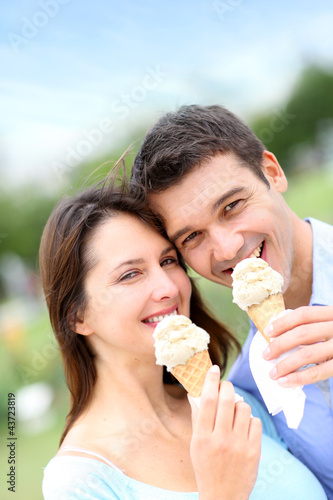 Couple in park eating ice cream cones