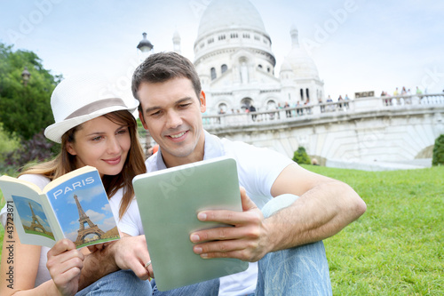 Couple using tablet in front of Sacre Coeur Basilica