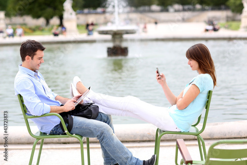 Couple relaxing in chairs in public park