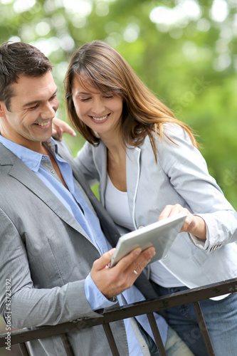 Couple standing in park with electronic tablet