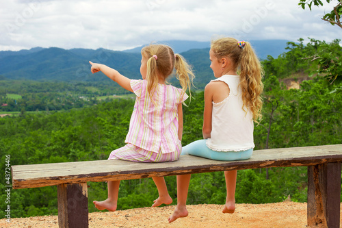 Two girls sit on the bench against the backdrop of the mountains