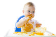 A young blue-eyed child feeding pumpkin puree