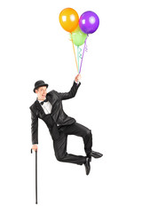 Magician flying up in the air and holding balloons