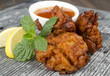 Onion Bhajis & chili sauce, lemon & mint leaves on a slate