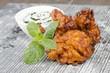 Onion Bhajis,  mint and yoghurt raita & mint leaves on a slate