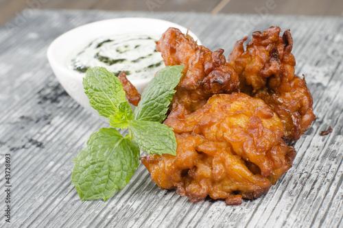 Onion Bhajis,  mint and yoghurt raita & mint leaves on a slate