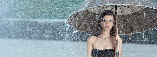 Beautiful  woman holding umbrella out in the rain