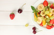 Fresh fruits salad on plate and berries on white wooden table