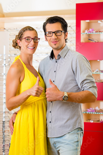 Junges Paar beim Optiker oder Brillengeschäft