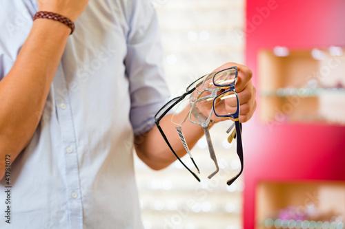 Junger Mann beim Optiker oder Brillengeschäft