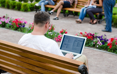 Man using a laptop in a public park