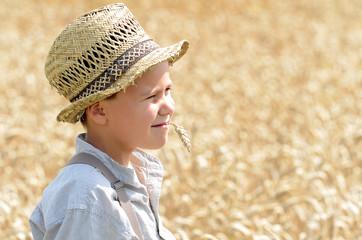 Junge mit Strohhut im Weizenfeld