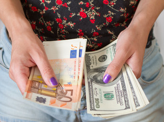 Woman's hands holding dollars and euros