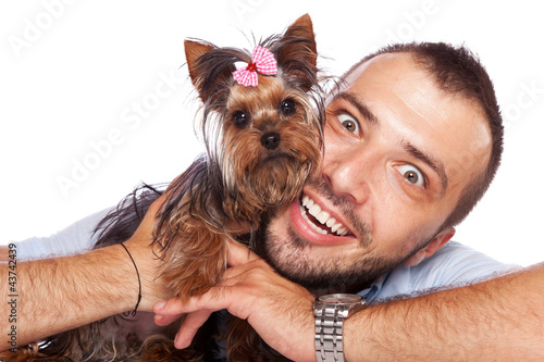 young man holding a cute yorkie puppy dog