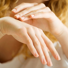 Closeup of woman hands applying cream