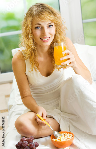 Young woman with orange juice eating at home