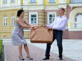 Stylish couple fighting over luggage