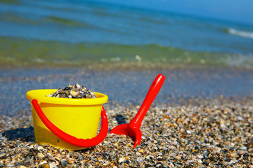 Plastic spade and bucket in sand