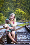Cute little girl with bear on railroad tracks