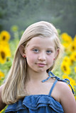 Beautiful little blonde, blue-eyed girl in sunflowers