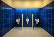 mens room interior with white urinals on blue tiled wall