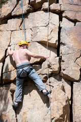 Vertical shot of a male rock climber on track