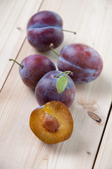 Whole and halved plums on wooden boards