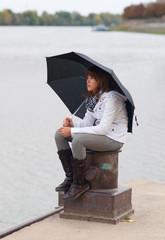 Beautiful smiling redhead teenage girl sitting on the dock