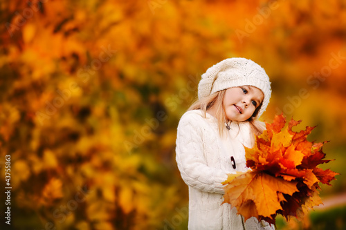 Cute little girl with autumn leaves in the park