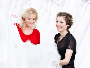 Designer and the client have a good look at the wedding dress