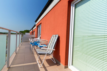 Summer sun at apartment balcony with deck chairs