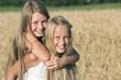 Zwei Mädchen haben Spaß im Getreidefeld
