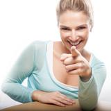 Frau zeigt mit Finger in Kamera