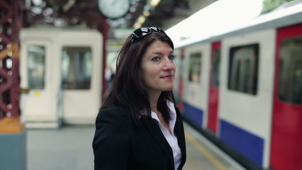 Happy businesswoman waiting for a train in the city