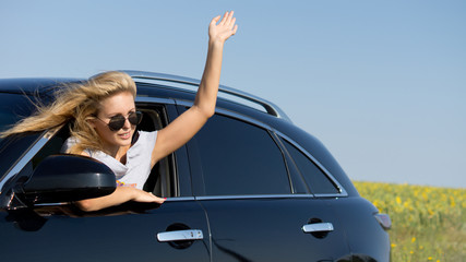 Woman leaning from car window waving