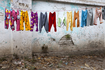 colorful kid`s pants are drying after laudry on the street